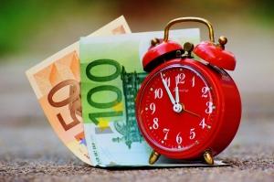 een wekker met een briefje van 50 en 100 euro