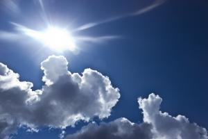 een lucht met wolken en een felle zon