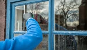 iemand die een raam schoonmaakt