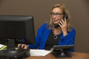 een vrouw achter een computer die aan het bellen i